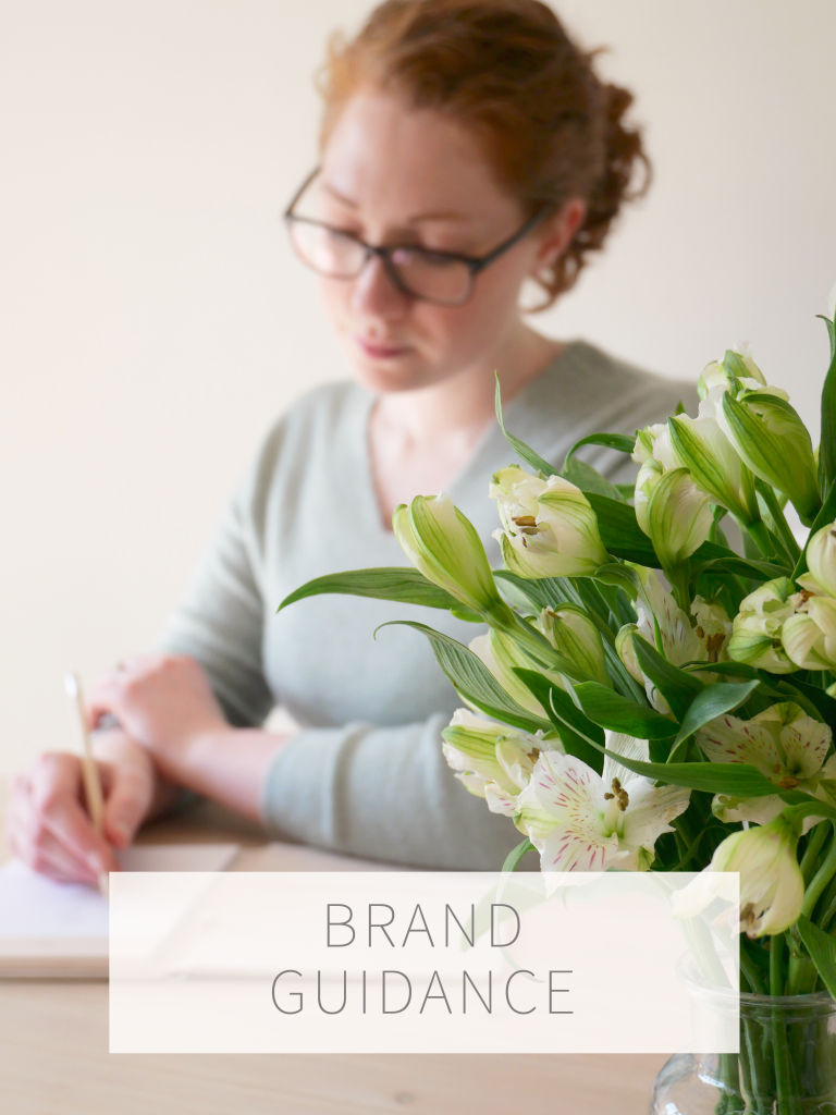 Brand guide, Kerri Awosile making notes at desk with flowers in foreground