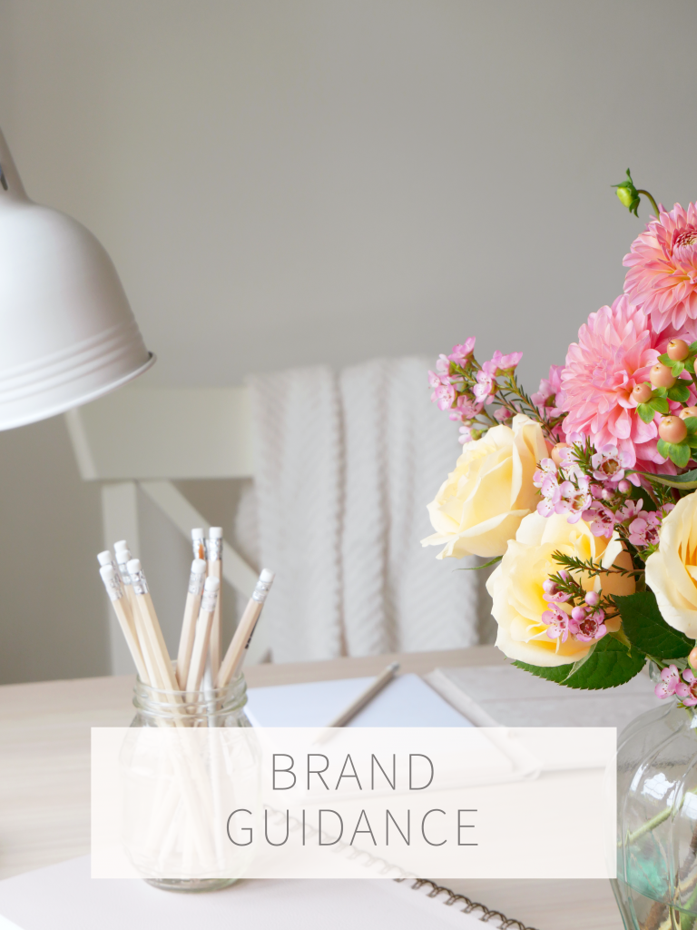 Brand Guide, Kerri Awosile's desk with pencils, notebook, and pink and peach flowers