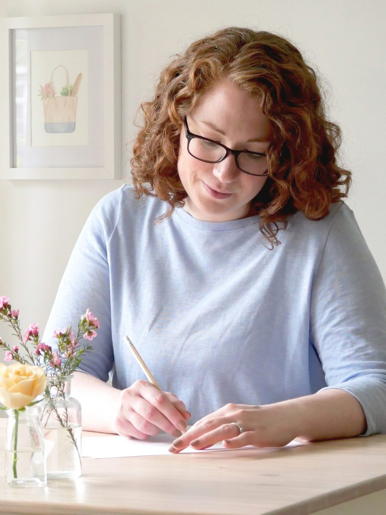 Brand guide consultant, Kerri Awosile at her desk writing, with peach and pink flowers in foreground