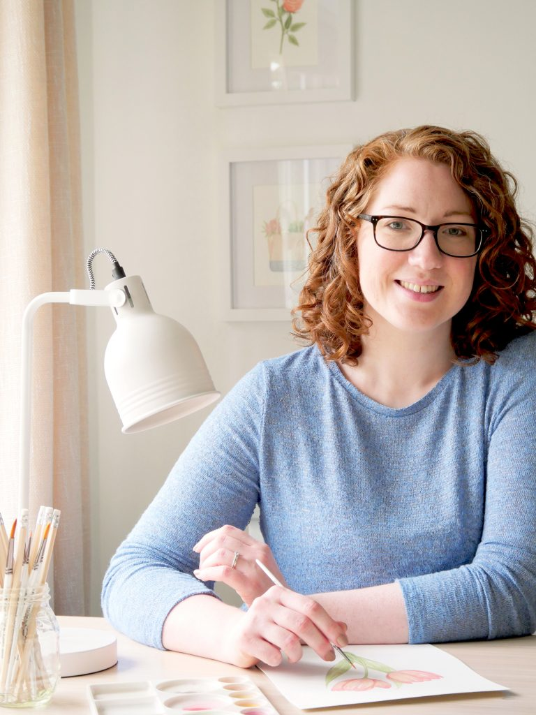 Surrey UK based brand designer and artist, Kerri Awosile, painting at desk with blue top, white lamp, pencils and paint brush and palette, and smiling to camera