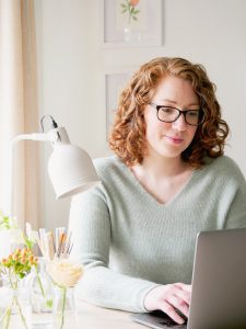 Brand designer and artists, Kerri Awosile typing on Macbook at desk with lamp and flowers