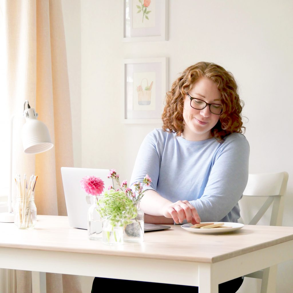 Kerri Awosile at desk with laptop, lamp, pencils, and flowers, with paintings on wall behind, and biscuits on a plate
