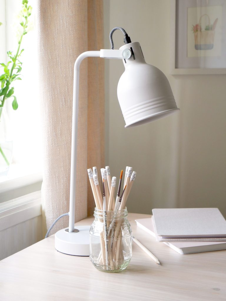 Rebrand designer, Kerri Awosile's desk with white lamp, pencils, notebooks, and green and white flowers