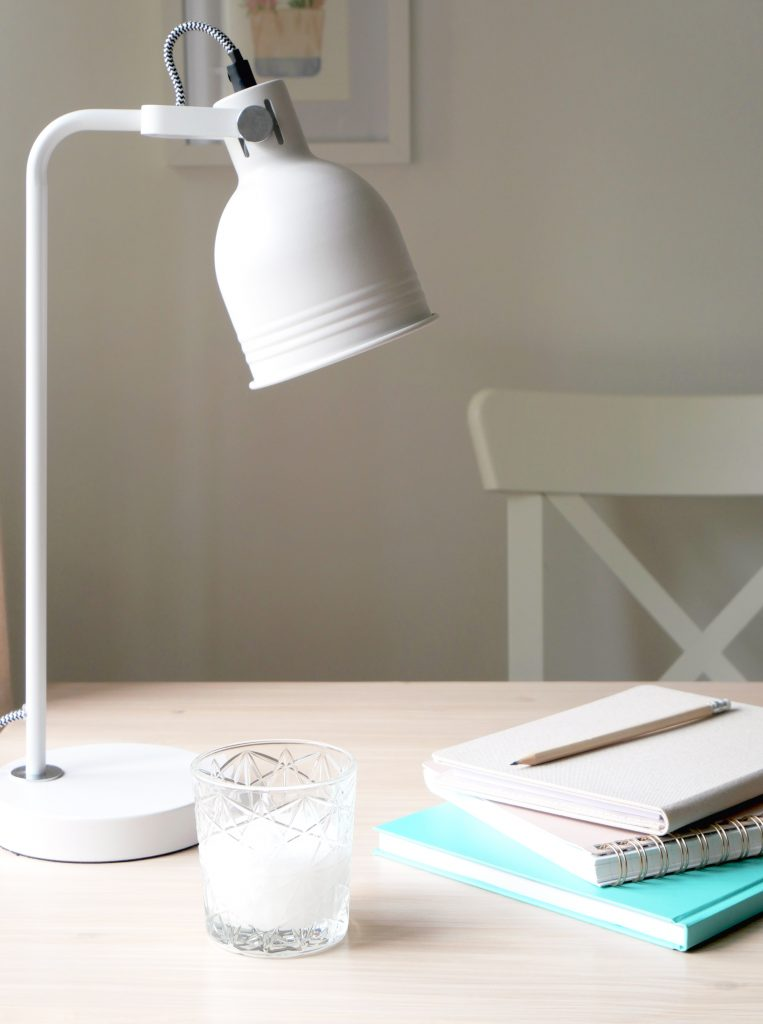 Small business branding design, Kerri Awosile's desk with white lamp, candle, and turquoise and neutral notebooks, and pencil