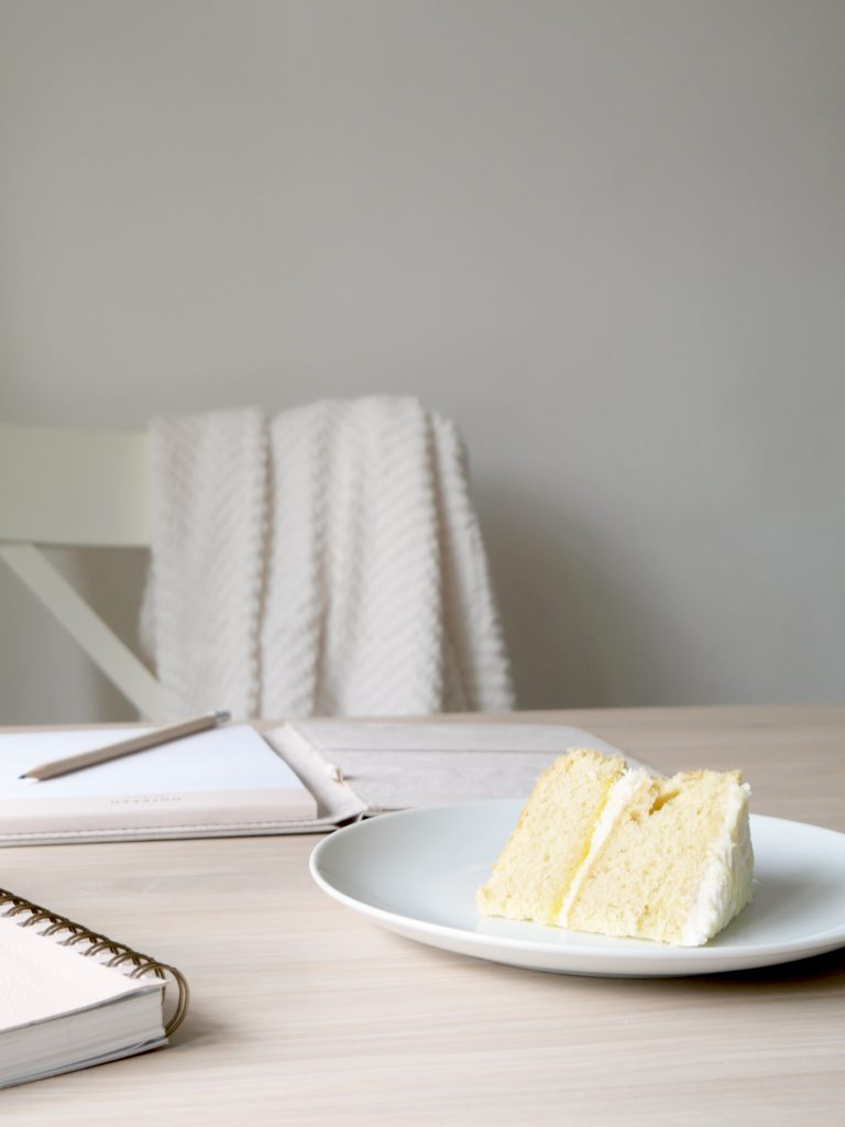 neutral desk, notepads, pencil, and blanket, with lemon drizzle cake on a white plate