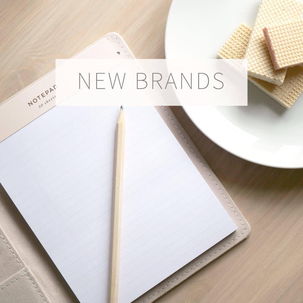 New brands photo link with notebook, pencil, and biscuits on desk