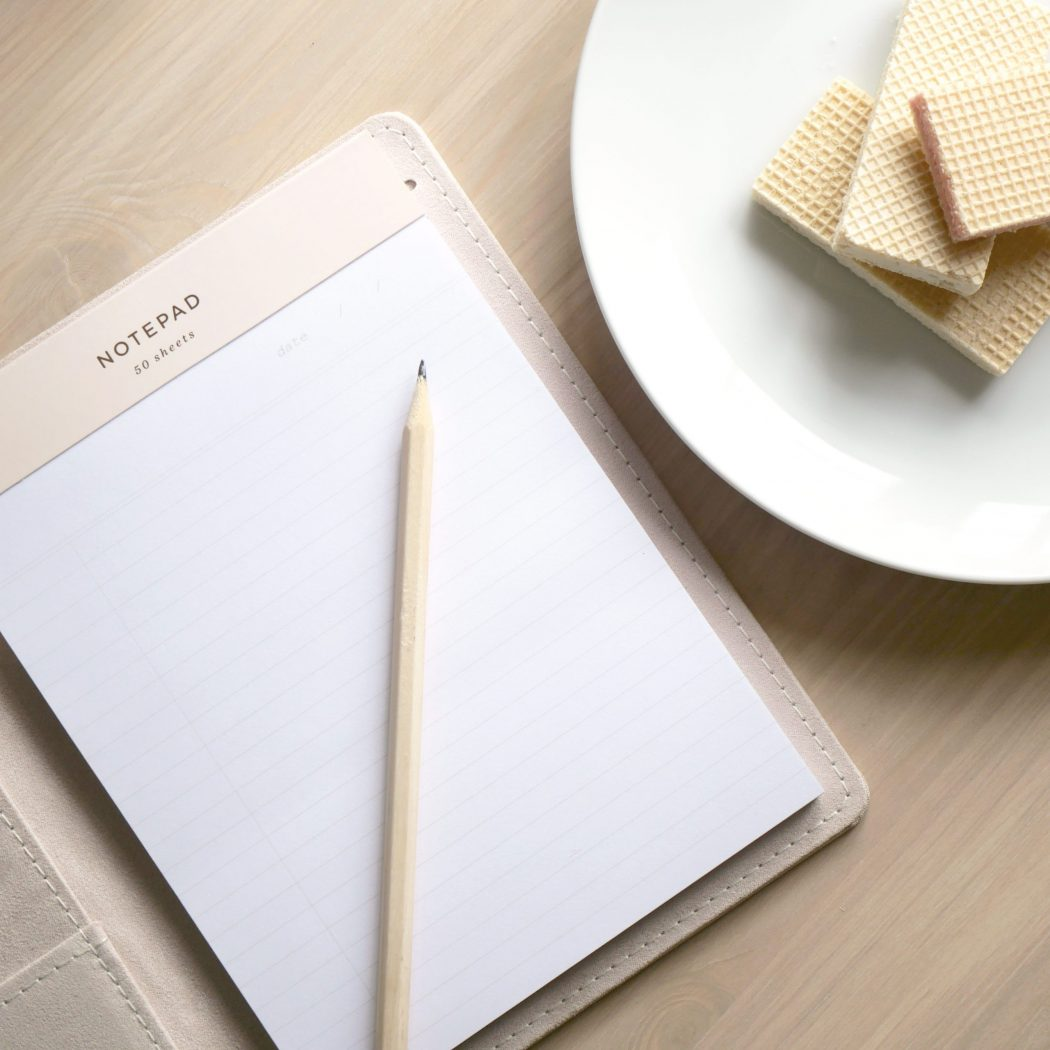 notebook, pencil, and biscuits on desk